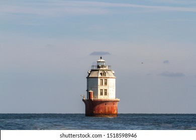 Point No Point Lighthouse in Chesapeake Bay off coastline of rural Virginia against blue skies.
