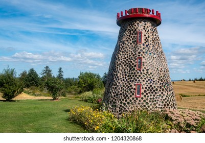 Point Prim (PEI), Canada: September 7, 2018: Group of Structures Constructed with Bottles and Mud at Hannah's Bottle Village, Beside a Hay Field