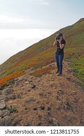 Point Reyes National Seashore, California - 10/14/2015: Woman hikes and photographs the rugged landscape of Point Reyes National Seashore in northern California.