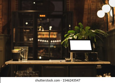 Point of sale POS touch terminal with white screen display, thermal printer and cash drawer. View from behind the waiter's counter cashier. Evening. Bokeh.