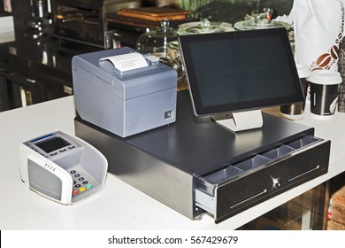 Point of sales computer terminal with touch screen tablet, cash register, mobile printer and card payment on a counter at a coffee shop.