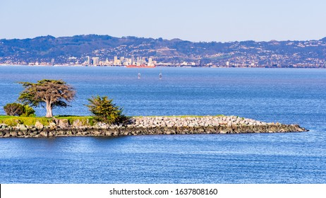 Point San Bruno Park jetty on the shoreline of San Francisco Bay; Port of Oakland, Oakland city skyline and residential neighborhoods built on the hills of East Bay visible in the background