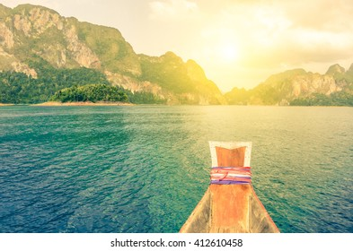 Point of view of Cheow Lan lake from long tail boat - Khao Sok National Park in Thailand - Adventure travel concept with wanderlust feelings - Enhanced sunflare halo with vivid vintage filter