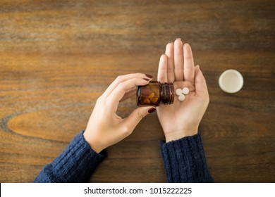 Point of view of female spilling pills onto hand over wooden table