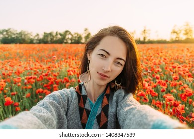 Point of view image of smiling beautiful young woman taking photo selfie in poppy flower field in summer.