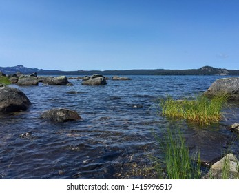 Point of view landscape from a kayak of crystal blue water, rocks and mountains in the distance at Waldo Lake in Oregon