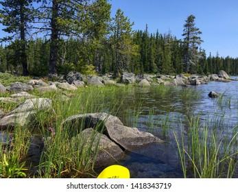 Point of view landscape of water, an oar, plants and stones in Waldo Lake in Oregon