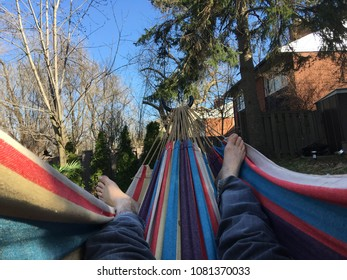 Point of view legs and bare feet in a backyard hammock.