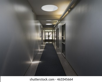 Point of view looking down empty offices hallway toward glass doors. / Hallway with Direct and Indirect Light
