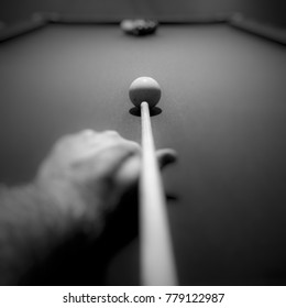 Point of view looking down pool stick aimed at cue ball. Focus is at end of stick and cue ball. Keep your eye on the ball. Focus on what matters.