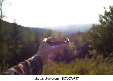 point of a view, mans hand holding a cup of coffee outdoors on a hiking trip, view on a mountain landscape