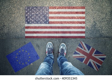Point of view of a person legs standing in front of USA, UK and EU Flags painted on city asphalt street ground.