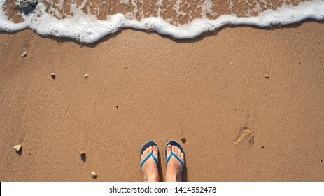 Point of view photography of beautiful female legs with natural pink nude look pedicure wearing rubber colorful flip flops standing alone at sandy summer sea beach. Happy holidays and travel concept.