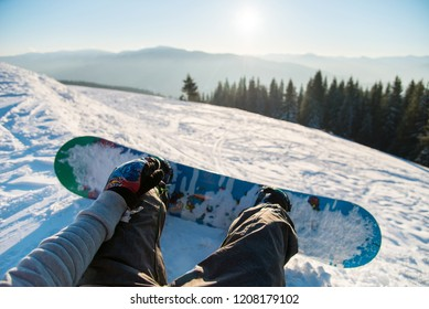 Point of view shot of a female snowboarder lying on the snow on the slope relaxing after riding, enjoying stunning view of winter mountains and sunset POV concept