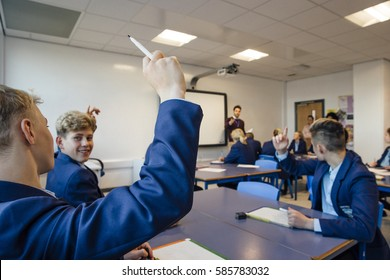 Point of view shot of a high school lesson where the teacher has asked a question and some students have their hands up to answer.
