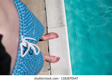 Point of view shot, looking down at a man's feet shirtless wearing blue swimming trunks standing on the edge of an outdoor swimming pool. Caucasian man in swimming suit standing at the edge of pool.