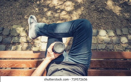 Point of view shot of a man sits on a bench in the park and holding a take away coffee
