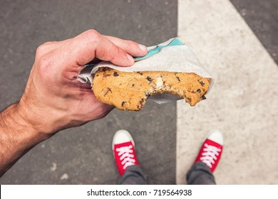 Point of view shot of a man standing along at the street and eats a cookie