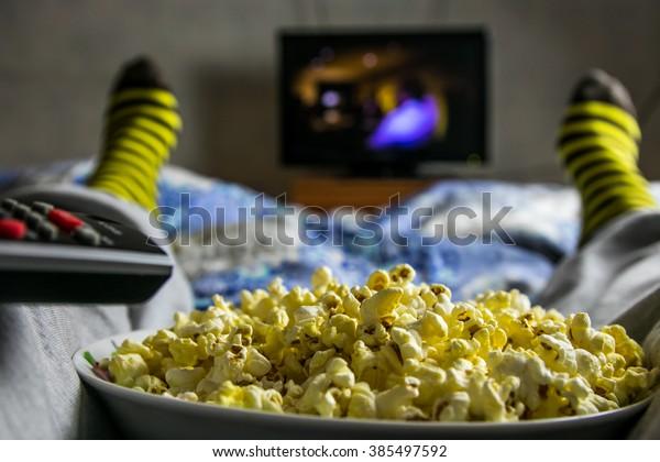 Point-of-View-TV ansehen. Man sieht sich einen Film mit Popcorn an. Fernbedienung
