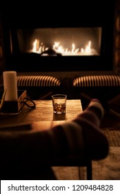 Point of view whiskey on ice drink with warm fireplace glow.