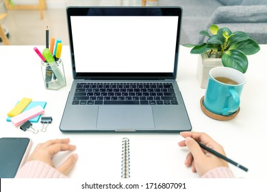Point of view of young asian girl sit on desk and learn at home living room in concept of romote learning, virtual online, self isolated quarantine lifestyle in asia. White blank screen.