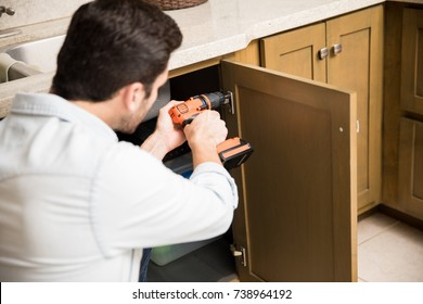 Point of view of a young handyman using a power drill to fix a door in a kitchen cabinet
