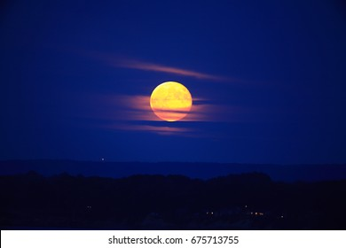 The Point At Which Twilight Turns To Night, A Slightly Cloud Veiled Harvest Moon Rising over Erie Pennsylvania Looking Across The Bay Towards Land, USA