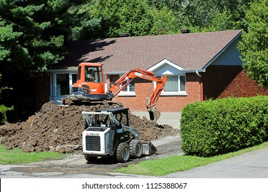 "Pointe Claire, Quebec/Canada - August 12, 2015"":  A suburban bungalow being excavated due to  water infiltration or other issues.  Can be used to illustrate foundation or basement problems"