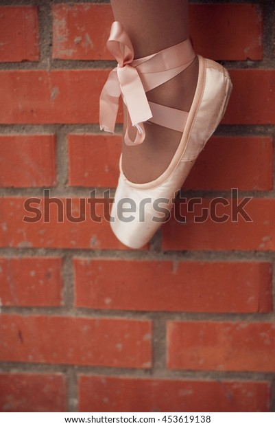 Pointe Shoes dancers on a brick wall