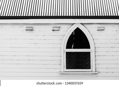 Pointed arch window in weatherboard church with corrugated iron roof