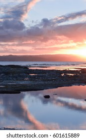 Pointed cloud shapes around a sunset at twilight reflected in the beach rock pools below, Gisborne, New Zealand.