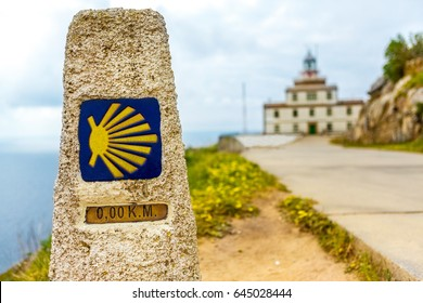 A pointer for the orientation of the Camino de Santiago pilgrims in Cape Finisterre. Finish zero Kilometers. In the background a lighthouse (faro) and an ocean. buen camino peregrino