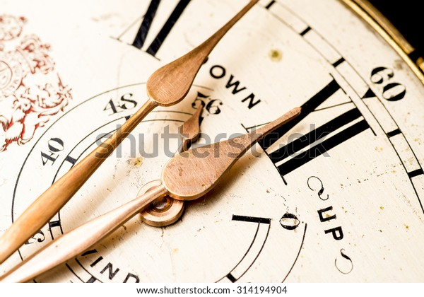 pointers reaching twelve of an ancient marine chronometer