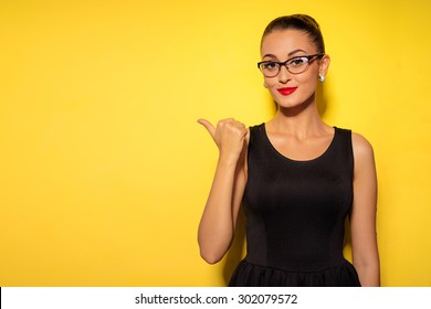 Pointing copy space. Bright studio portrait of attractive young woman pointing copyspace with her thumb.