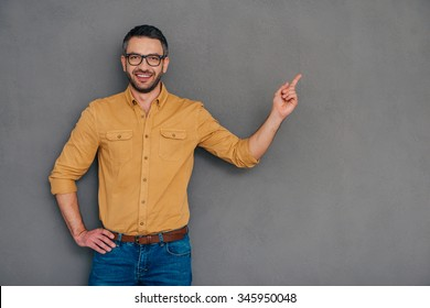 Pointing copy space. Confident mature man pointing away and smiling while standing against grey background