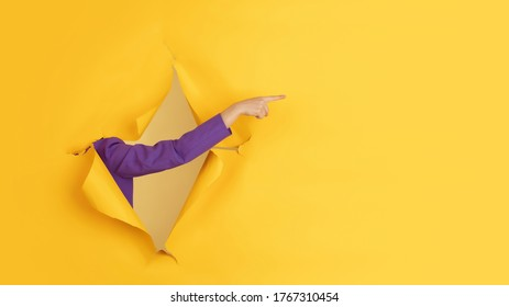 Pointing. Female hand gesturing in torn yellow paper hole background. Breaking on, breakthrought. Concept of business, finance, shopping, proposal, sales, ad. Copyspace Promotions discounts