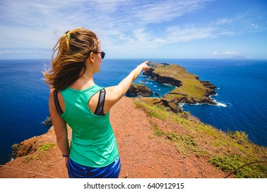 Pointing a finger at the Atlantic ocean at Ponta do Furado cape in Madeira