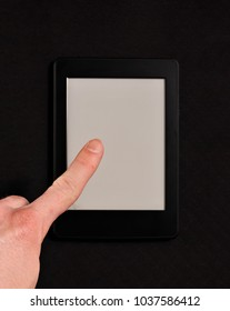 Pointing finger to  E-book reader with white clear screen, on black textured background.
