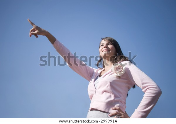 Pointing girl. On blue sky background.