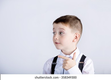 Pointing to right little boy isolated over yellow background.
