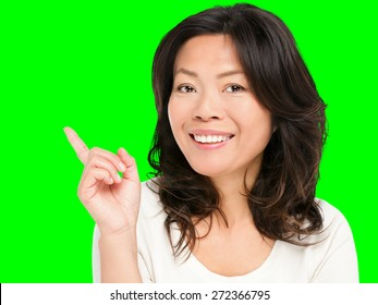 Pointing showing Asian woman. Middle aged Chinese Asian woman pointing and showing smiling happy. Female model in her early 50s isolated cutout on green chroma key background.