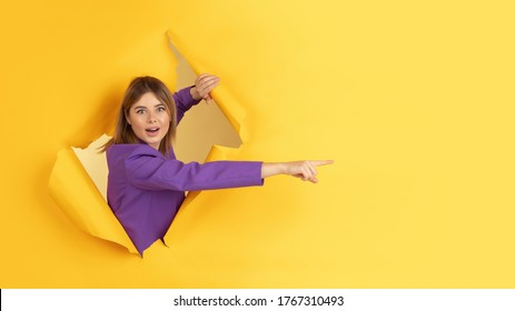 Pointing, showing. Cheerful caucasian young woman poses in torn yellow paper background, emotional and expressive. Breaking on, breakthrought. Concept of human emotions, facial expression, sales, ad.