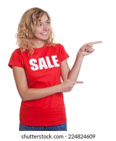 Pointing woman with blond hair in a sale shirt