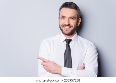 Pointing your product. Portrait of handsome mature man in shirt and tie pointing copy space and smiling while standing against grey background