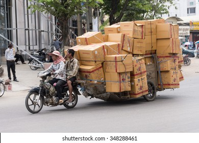POIPET - Oct 31: Workers transport goods by motorbike and cart in the Thai-Cambodian border town on October 31,2015  in Poipet, Cambodia. The border town has a large export trade with Thailand.