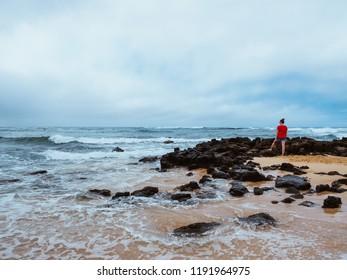 POIPU, HAWAII - AUGUST 9, 2018: Woman overlooking volcanic rocks on beach in Poipu, Kauai