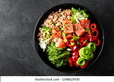 poke bowl of brown rice, trout or salmon fillet, Chuka Seaweed Salad, sesame and fresh vegetables on dark background, top view, copy space, healthy food trend