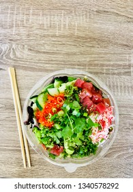 Poke Bowl with Chopsticks Ahi Tuna Salmon Salad Greens and Rice Top View on Wooden Table