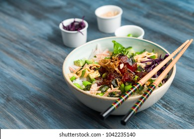 Poke bowl with chopsticks and ingredients. Poke is a traditional Hawaiian dish influenced by japanese and asian cuisine. Ahi poke is made of raw tuna chunks tossed over rice & topped with vegetables.