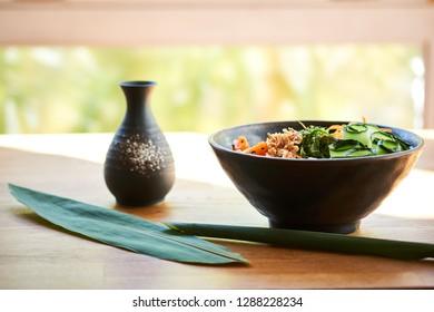 Poke bowl, chopsticks and Japanese alcoholic drink sake on table. Traditional Hawaiian and Japanese cuisine. Healthy food.